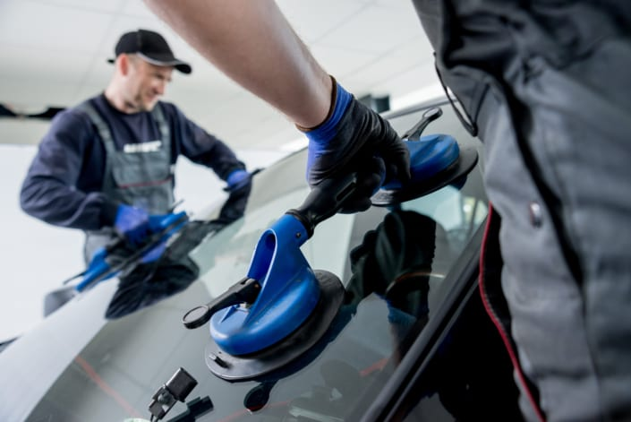 Autoglass Replacement Brisbane - Automobile special workers replacing windscreen or windshield of a car in auto service station garage.